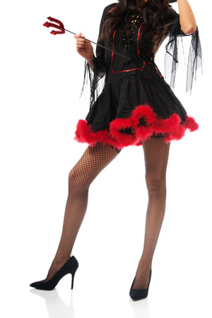 Close up on woman legs wearing devil clothes, holding trident. photo
