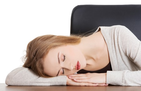 Tired woman slepping on desk. photo