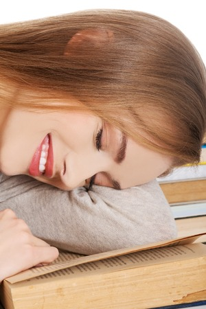 Tired woman slepping on books. photo