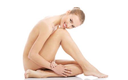 femme se deshabille: Vue de c�t� femme nue assise sur le sol.
