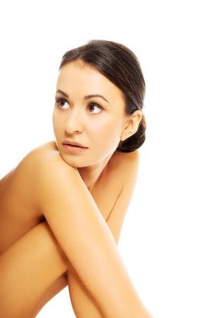 mujer desnuda sentada: Portrait of beautiful nude woman sitting and looking up.