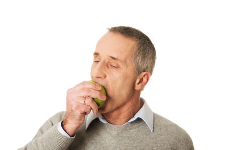 Portrait of mature man eating an apple. photo