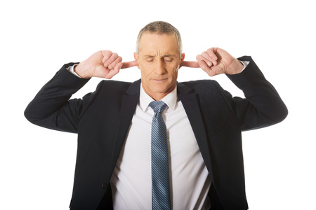 def: Portrait of businessman plugging his ears.