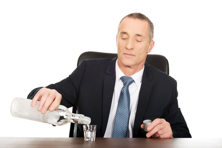 vodka: Businessman in office pouring vodka into a glass.