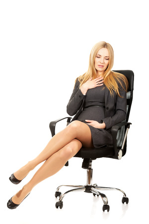Pregnant woman sitting on armchair suffering from nausea