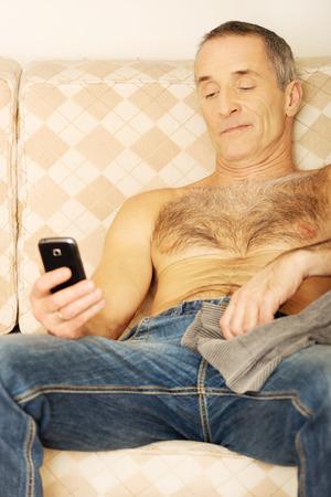 hombres sin camisa: Hombre guapo sin camisa en un sof� mirando su tel�fono inteligente. Foto de archivo