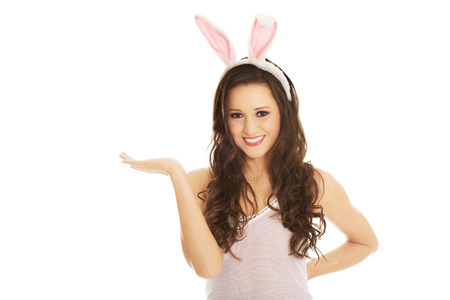 animal ear: Beautiful woman wearing bunny ears and presenting a copyspace
