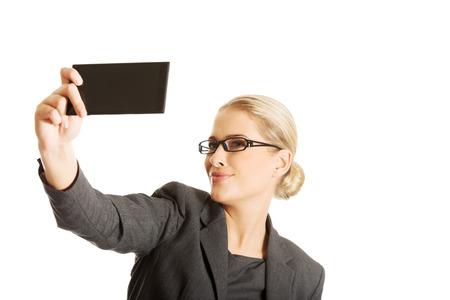 Businesswoman taking selfie with smartphone photo