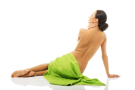 Back view woman sitting wrapped in towel. Stock Photo