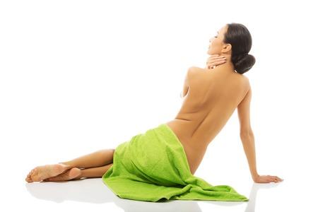 nude woman: Volver la vista mujer sentado envuelto en una toalla.