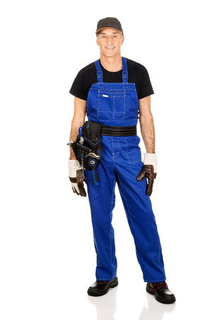 studio happy overall: Full length mature worker with tool belt.
