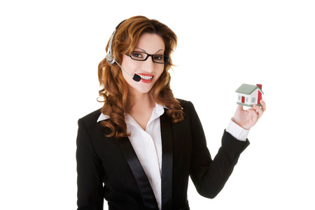 Happy smiling call center woman showing house model. photo