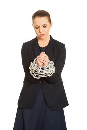 drudgery: Guilty businesswoman wrapped with metal chain. Stock Photo