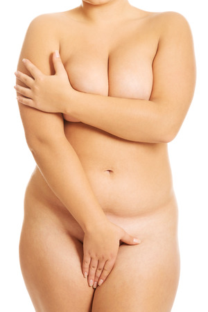 Undressed overweight woman covering intimate places