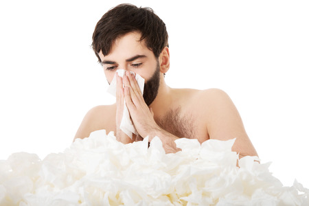 Sick man with a lot of tissues sneezing into handkerchief. photo