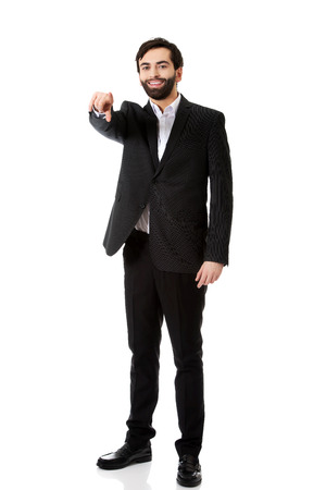 Happy businessman pointing his finger on you. photo