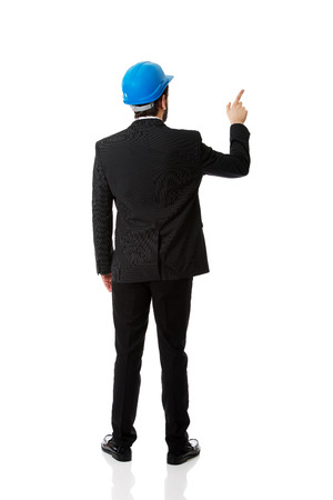 Businessman engineer with hard hat pointing up. photo