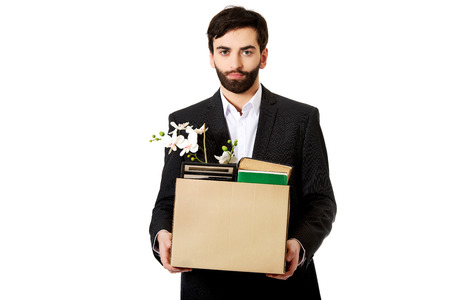 belongings: Fired businessman holding box with personal belongings.