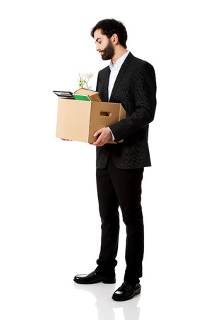 unemployed dismissed: Fired businessman holding box with personal belongings.
