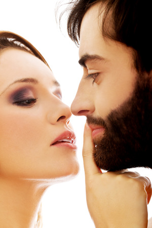 shushing: Young woman putting her finger on mans lips.