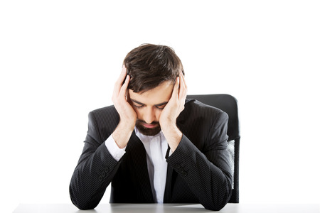 Tired businessman sitting at the desk. photo