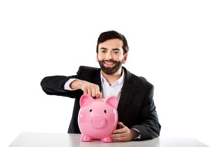 piggybank: Young successful businessman putting a coin to piggybank. Stock Photo
