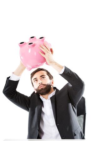 piggybank: Young businessman searching money in piggybank. Stock Photo