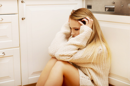 aloneness: Sad lonely young woman sitting in the kitchen at home.
