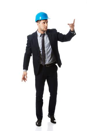 executive helmet: Happy handsome businessman in helmet points his finger up.
