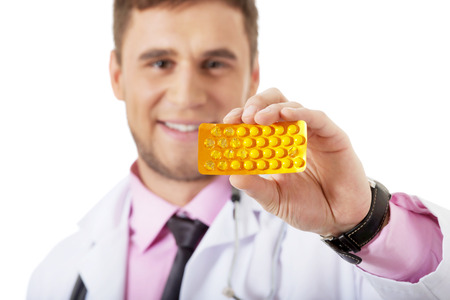 Male doctor or pharmacist holding pills. photo