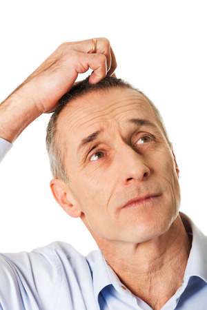 Mature confused man scratching his head. photo