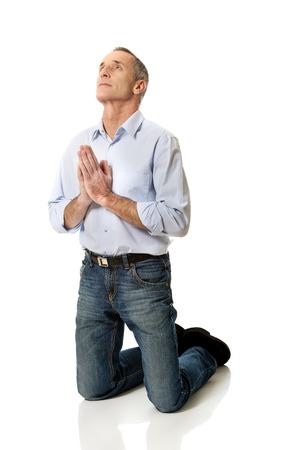 kneeling man: Man kneeling and praying to God. Stock Photo