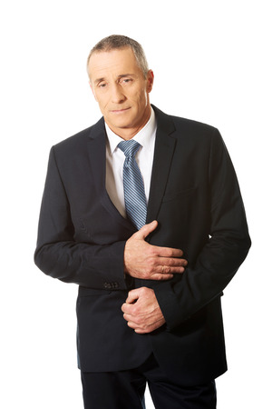 colitis: Mature businessman suffering from stomachache.