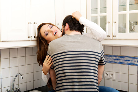Young couple kissing with desire in the kitchen. photo