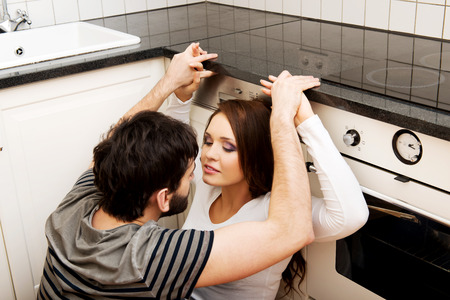 sex tenderness: Happy young couple embracing each-other in the kitchen. Stock Photo