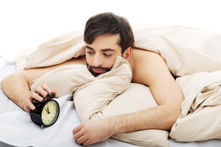 awakened: Exhausted man being awakened by an alarm clock in his bedroom.
