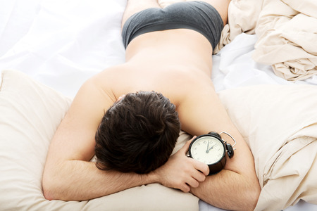 obudził: Wyczerpany człowiek budzi się budzik w swojej sypialni.