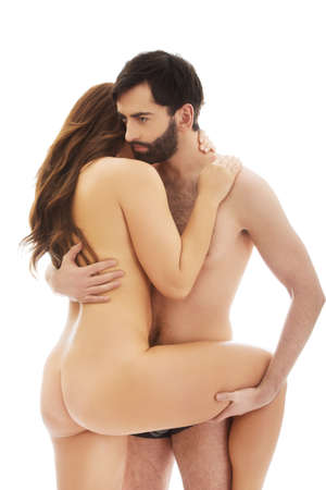 Handsome man embracing naked woman and holding her leg.