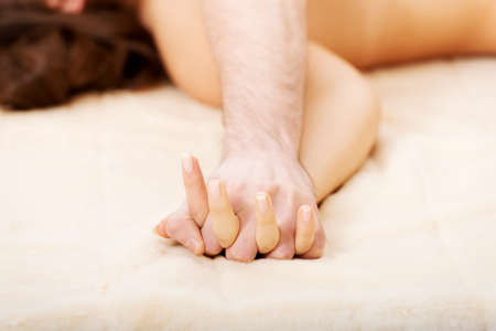 husbands and wives: Hands of playful couple lying on bed. Stock Photo
