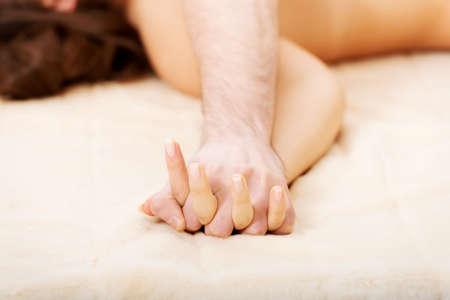 Hands of spielerisch Paar liegt auf dem Bett.