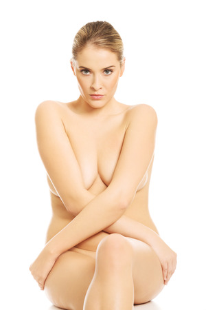 Close up of nude woman sitting with cross legs on something invisible. photo