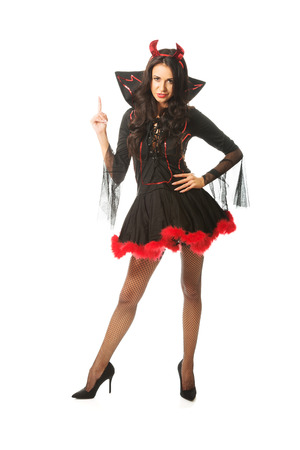 Portrait of a woman wearing devil clothes pointing up. photo