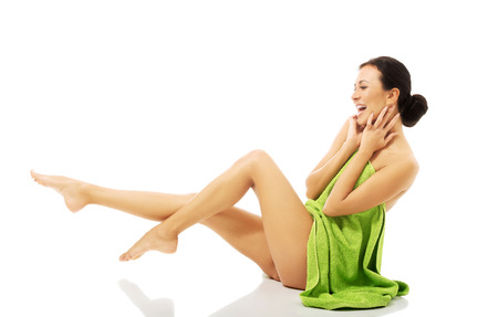 Laughing woman wrapped in towel with legs up. Stock Photo