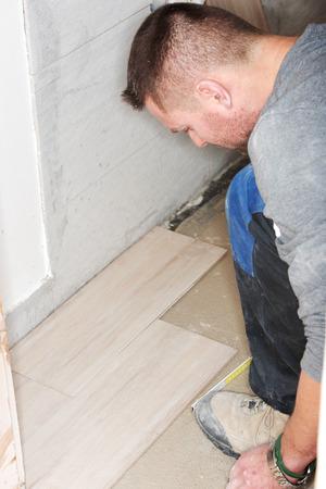 Tiler installs ceramic tiles at home. photo