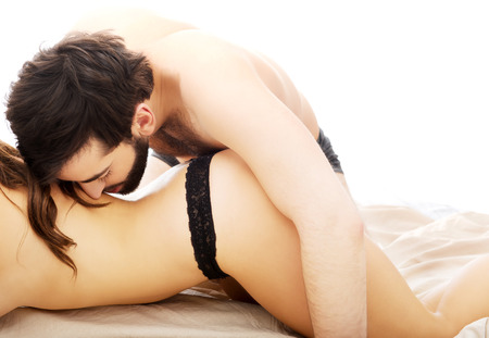 Young beautiful couple having foreplay in bedroom.