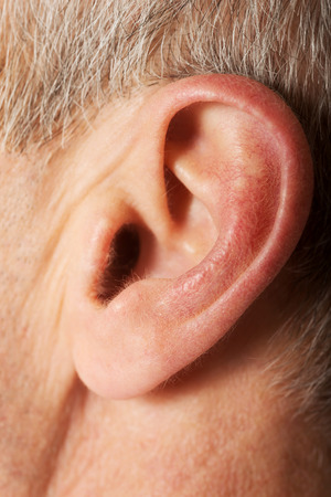 by ear: Close up on male ear.
