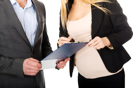 Working pregnant woman signing contract with her partner photo