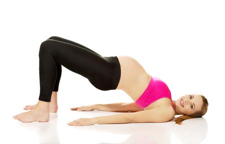 Calm pregnant woman exercising yoga.