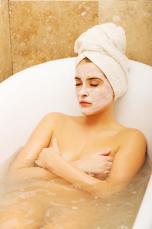 relaxion: Woman relaxing in bath with face mask, wearing towel on head.