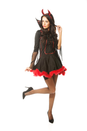 Full length devil woman standing with bended knee. photo